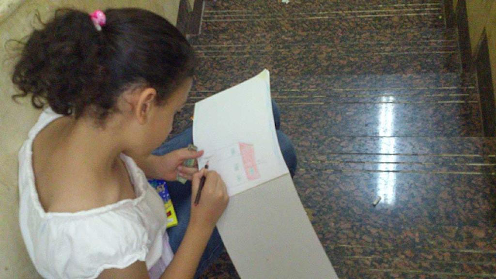 Sohas enda överlevande dotter, Sarah, ritar ett hem som inte längre finns. Foto: Sveriges Radio