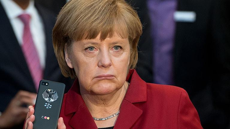 Tysklands förbundskansler Angela Merkel håller upp en mobiltelefon. Arkivfoto: Julian Stratenschulte/AP/TT.