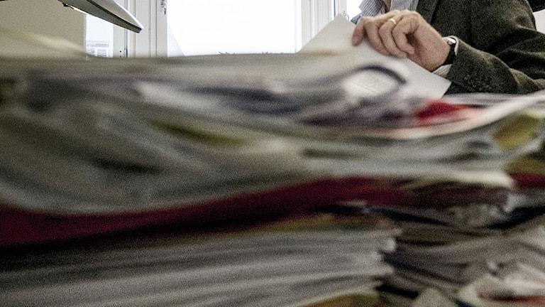 Massa papper och en hand. Foto: Magnus Hjalmarson Neideman/TT