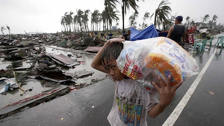 En pojke bär en påse med mat i staden Tacloban i Filippinerna. Foto: Aaron Favila/TT.