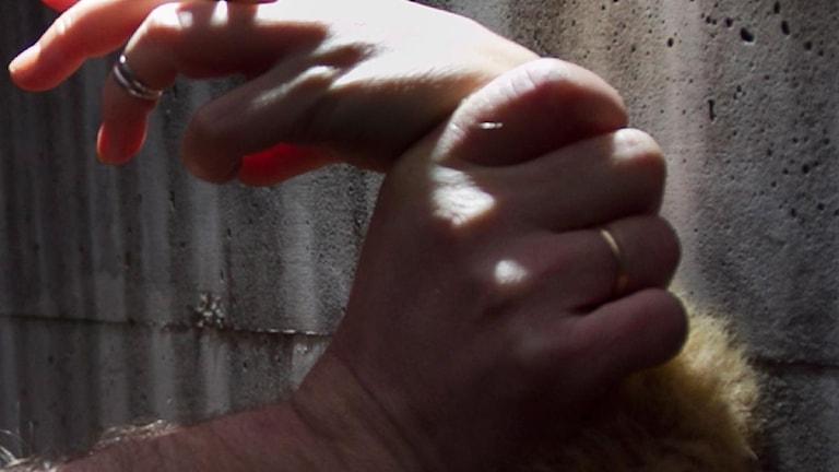 Manshand håller fast kvinnas handled.