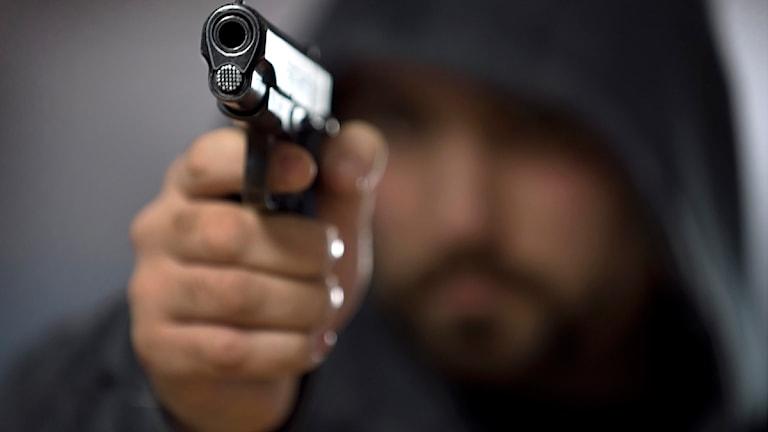 man i huva riktar pistol