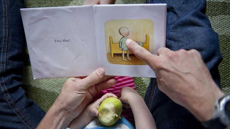 En pappa läser för sitt barn.