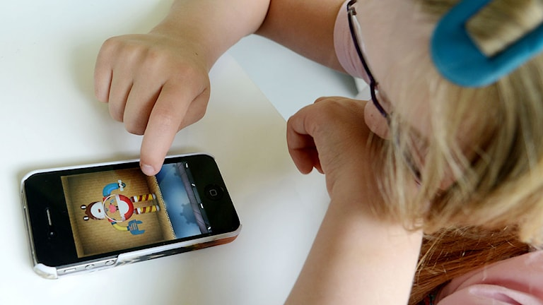 En liten flicka spelar på en mobiltelefon. Foto: Johan Nilsson/TT.