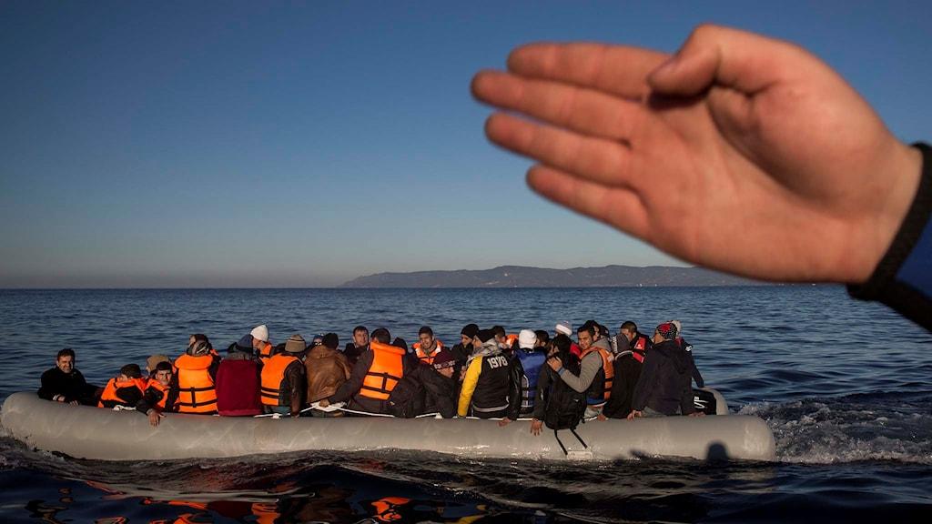 Flyktingar och migranter i en gummibåt.