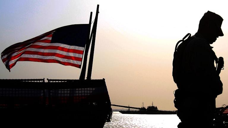 En amerikansk soldat syns i profil med en vajande flagga bakom sig. Foto: AP Photo/Hasan Jamali/ TT