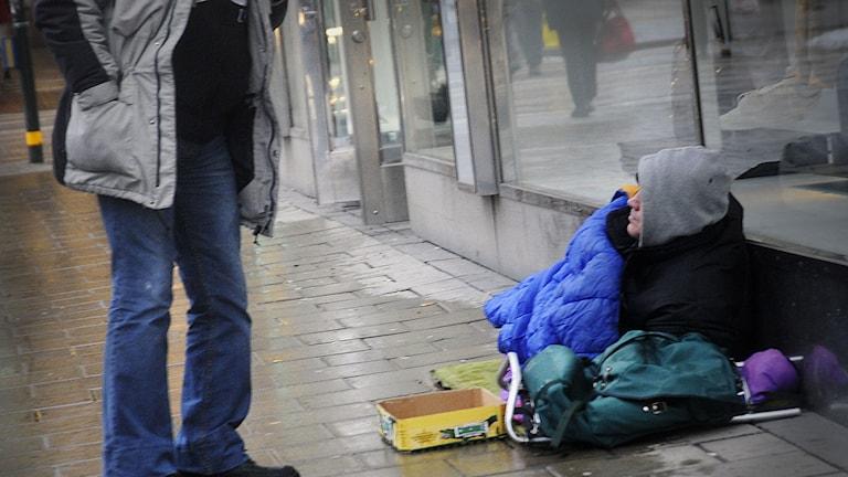 Man stannar och pratar med en tiggare i Stockholm. Foto: Hasse Holmberg/TT.