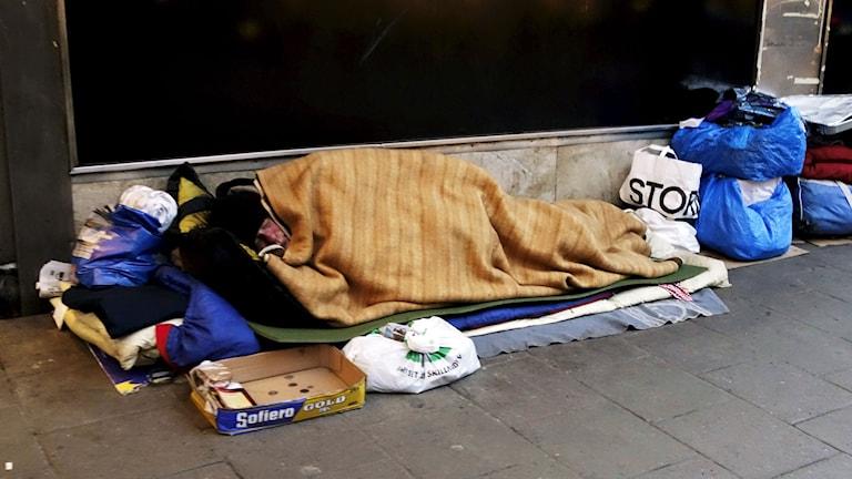 Tiggare ligger insvept i en filt vid en vägg. Foto: Hasse Holmberg/TT