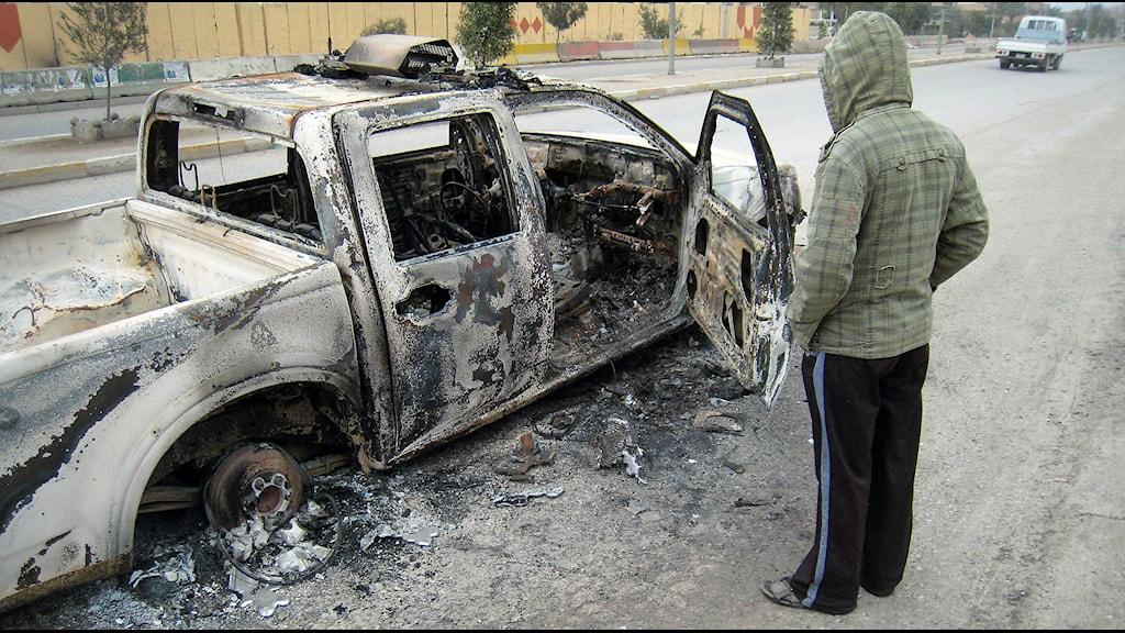 Nedbränd polisbil på huvudgatan i Falluja efter sammandrabbningar mellan säkrhetstjänsten och al-Qaidamän. Foto: TT.