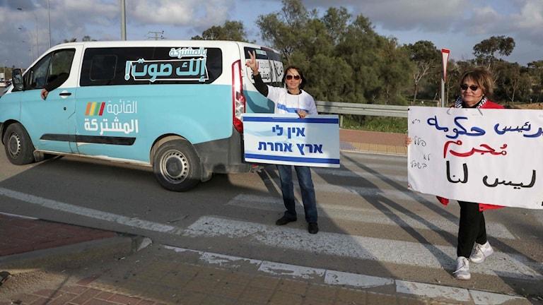 Israeliska demonstranter lyfter affischer mot premiärminister  Benjamin Netenyahu när en kampanjbuss för Arab Joint List passerar. Foto: Hazem Bader/TT.