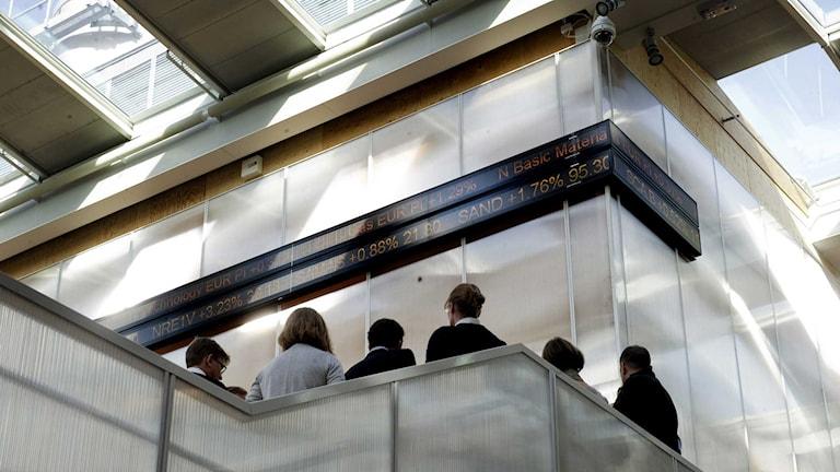 Öppet hus på Stockholmsbörsen Nasdaq OMX. Några personer står och tittar på börskurser. Foto: Jessica Gow/TT.