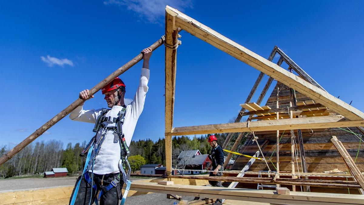 Byggnadsarbetare reser en stor träställning i bygget av Södra Råda nya träkyrka.