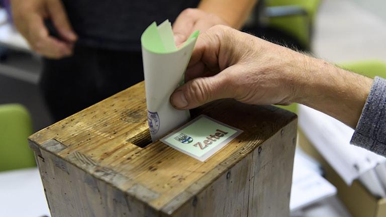 En väljare stoppar ned sin valsedel i en urna.