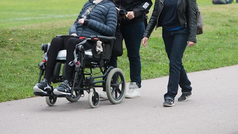 Två assistenter är ute och går med en tjej som sitter i rullstol.