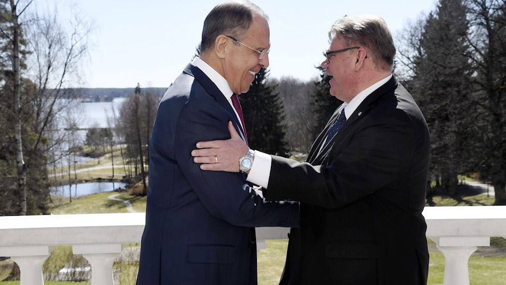Tvä män i kostym klappar om varandra.