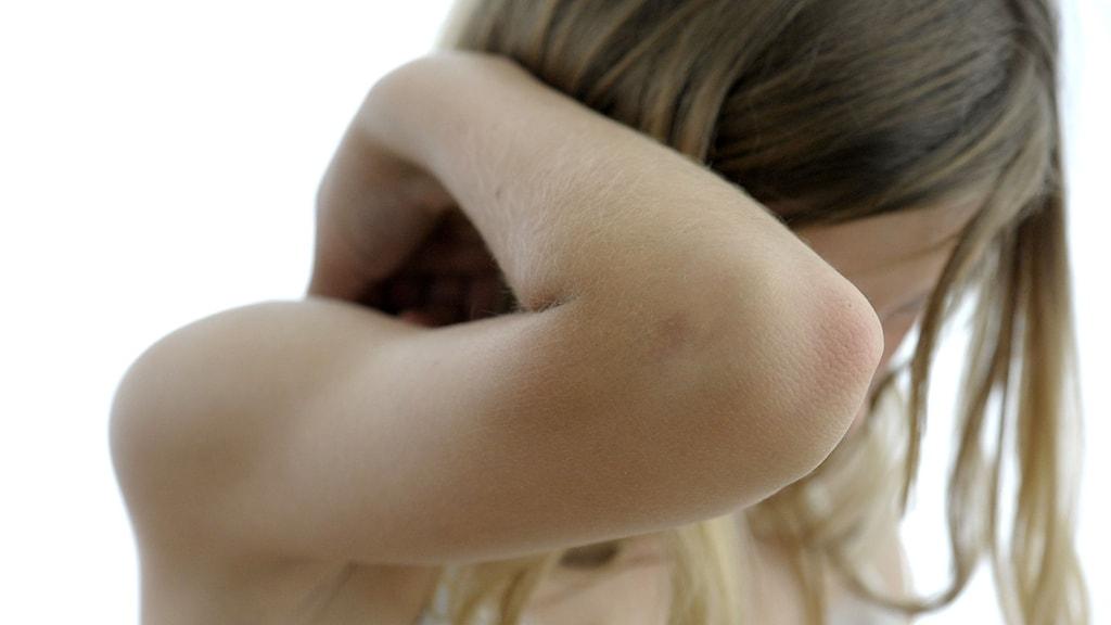 Armbågen på en flicka som håller upp armen som skydd för ansiktet. Foto: Janerik Henriksson / TT