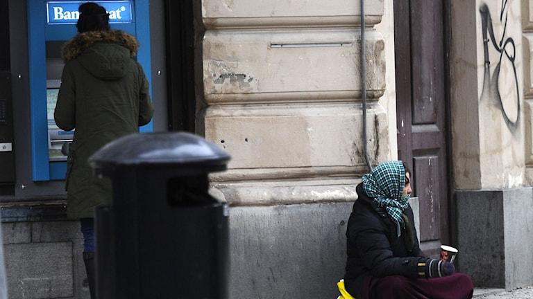 En kvinna tigger pengar på gatan.