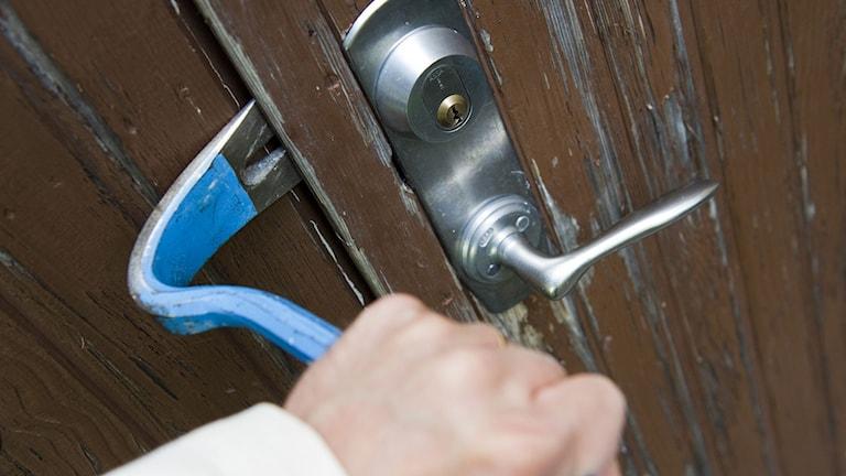 En inbrottstjuv bryter upp dörren till en bostad med hjälp av en kofot Foto: Henrik Montgomery/TT.