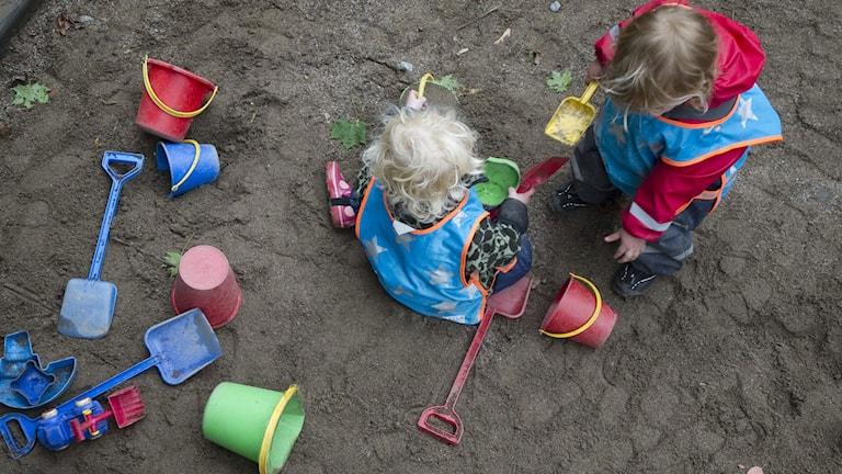 Barn leker i sandlåda.