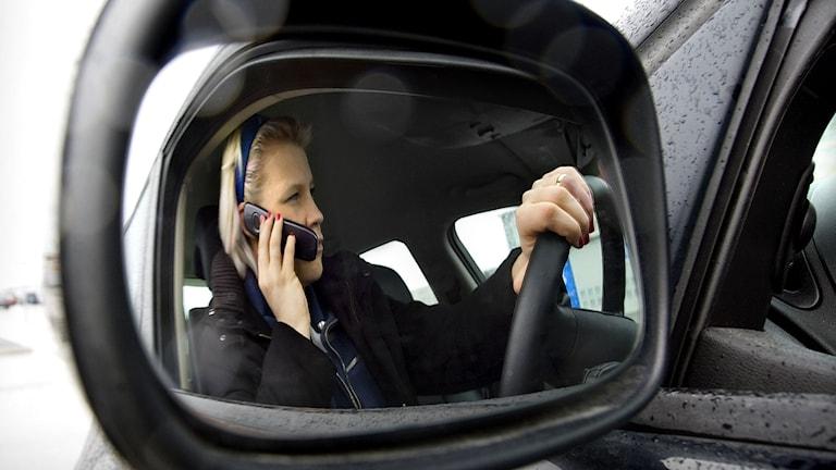En kvinna pratar i mobil medan hon kör bil. Foto: Claudio Bresciani/TT.