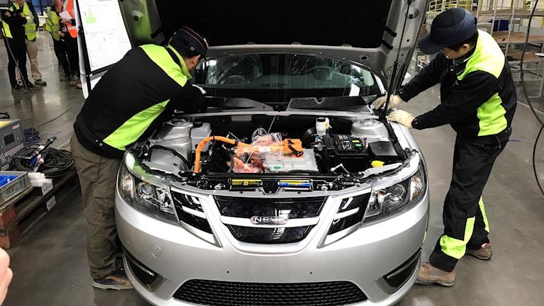 Två Nevsarbetare står och grejar inne i motorhuven på en elbil i företagets fabrik
