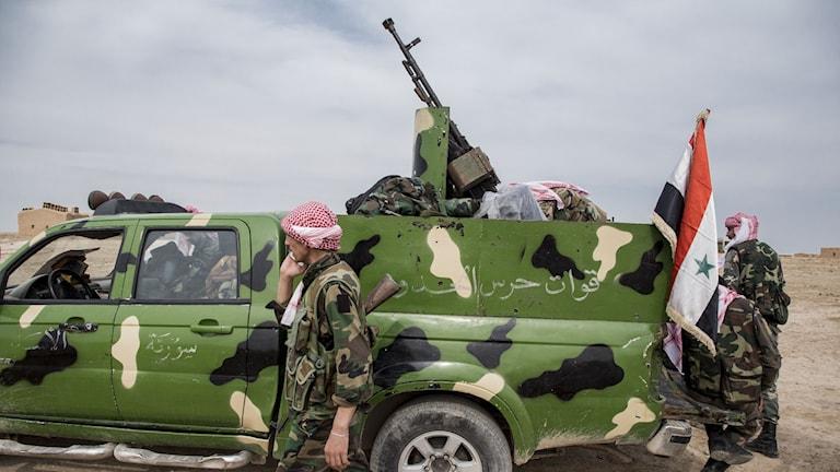 Militärfordon med syrisk flagga.
