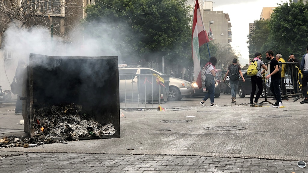 Papperskorg omkullvält på gata, rykande aska väller ut ur den. Människor med masker och protestplakat i bakgrunden.