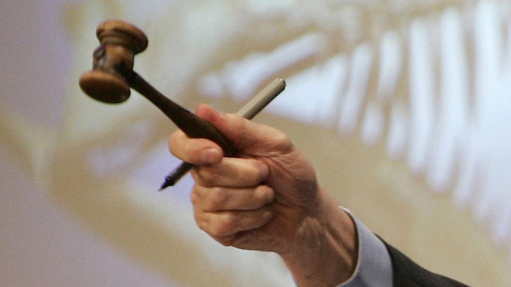 En hand som håller en auktionsklubba och en penna.