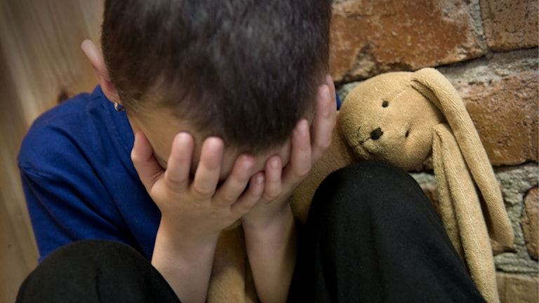 En ledsen pojke sitter och gråter och kramar sitt gosedjur.