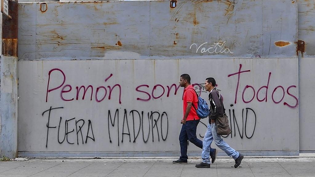 Caracas, venezuela, två personer går förbi vägg med anti-Maduro-klotter