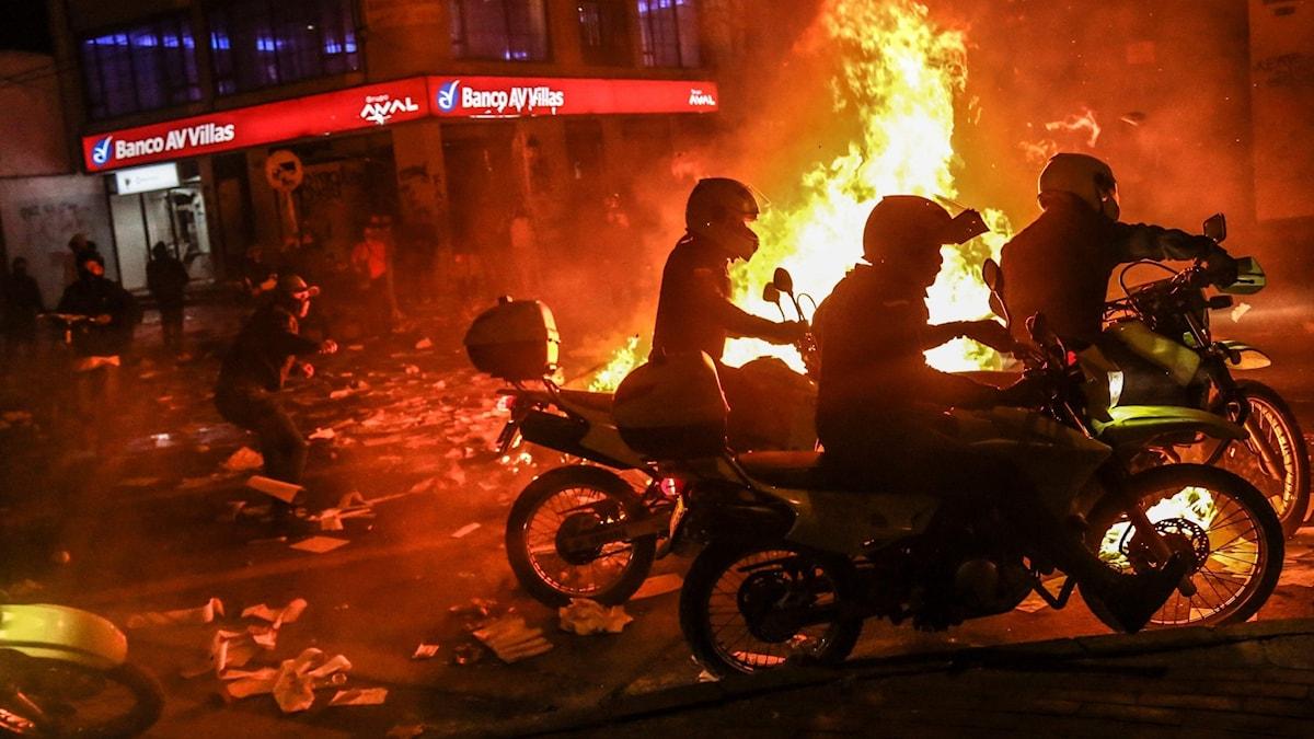 Demonstranter kastar sten på motorcykelpoliser under demonstrationerna i Bogotá.