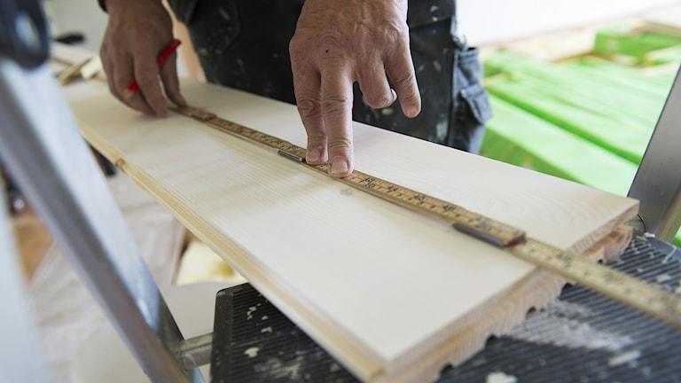En snickare som lägger ett trägolv mäter upp en golvplanka med penna och tumstock. Foto: Fredrik Sandberg/TT.