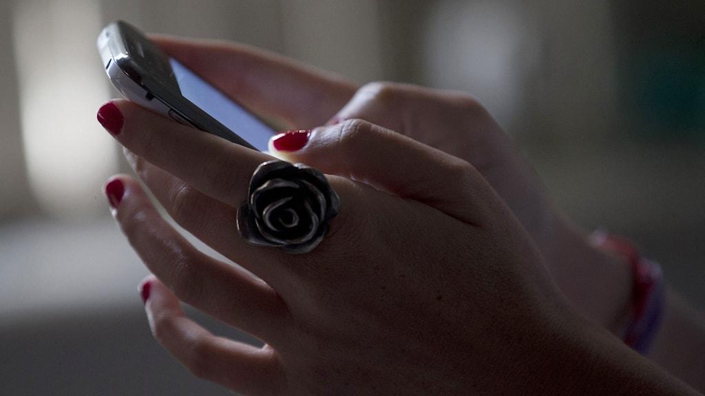 Kvinna håller i mobil. Foto: Silvia Izquierdo/TT.