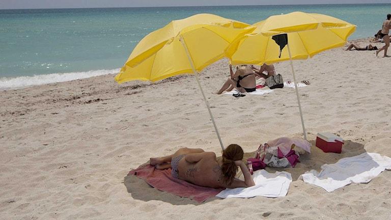 Kvinna under ett parasoll på en strand.