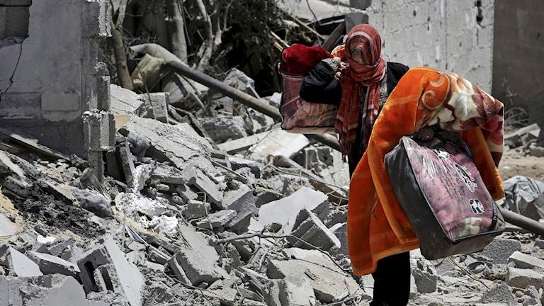 Kvinna i Gaza vandrar bland ruiner.