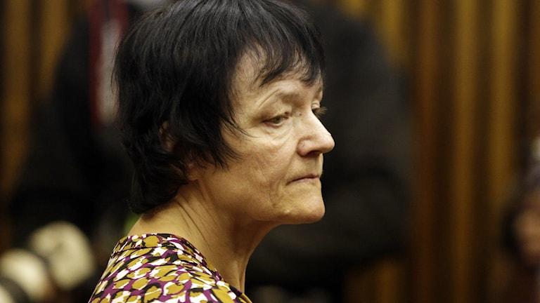 Kvinna i mörkt kort hår tittar neråt.