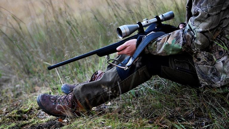 Jägare sitter i gräs med vapen.