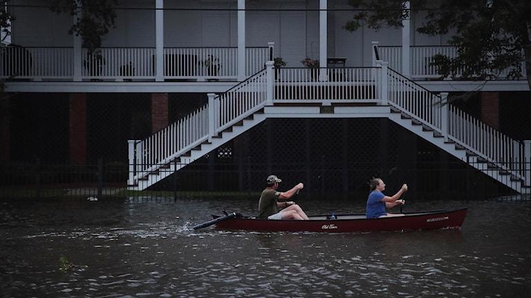 Kanot paddlar förbi ett hus på en översvämmad gata.