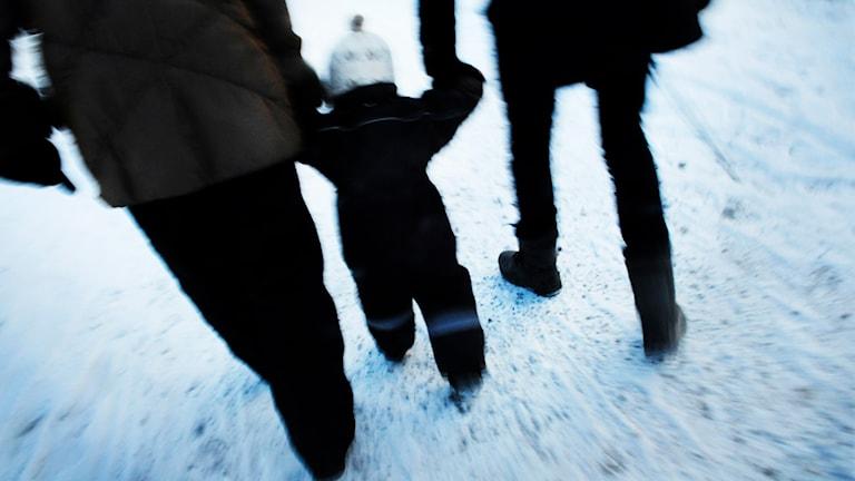 Barn går hand i hand med två vuxna. Foto: TT