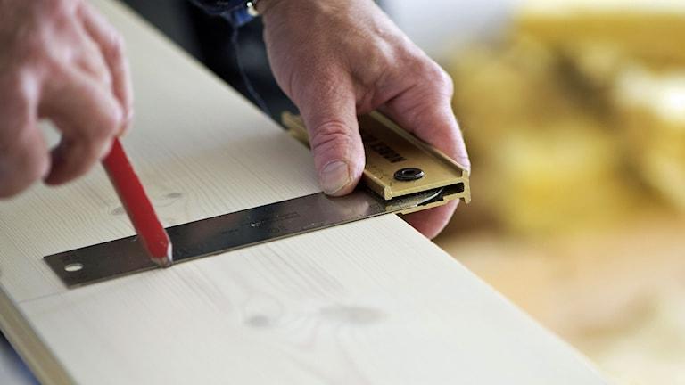 En snickare med vinkeljärn ritar med en penna på en planka. Foto: Fredrik Sandberg/TT.