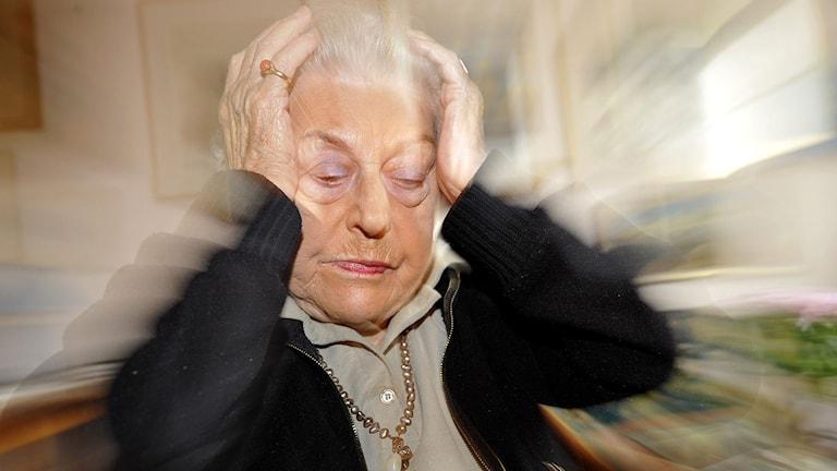En äldre kvinna med migrän håller händerna runt huvudet. Foto: Bertil Ericson/TT.