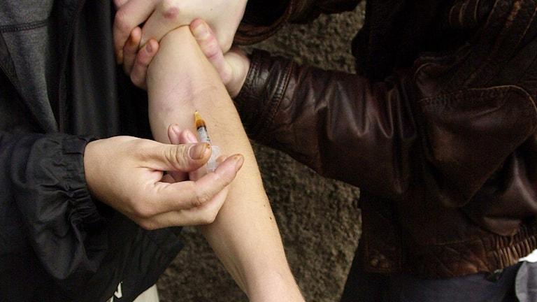 Två män hjälps åt att injicera heroin. Foto: Erlend Aas/TT.