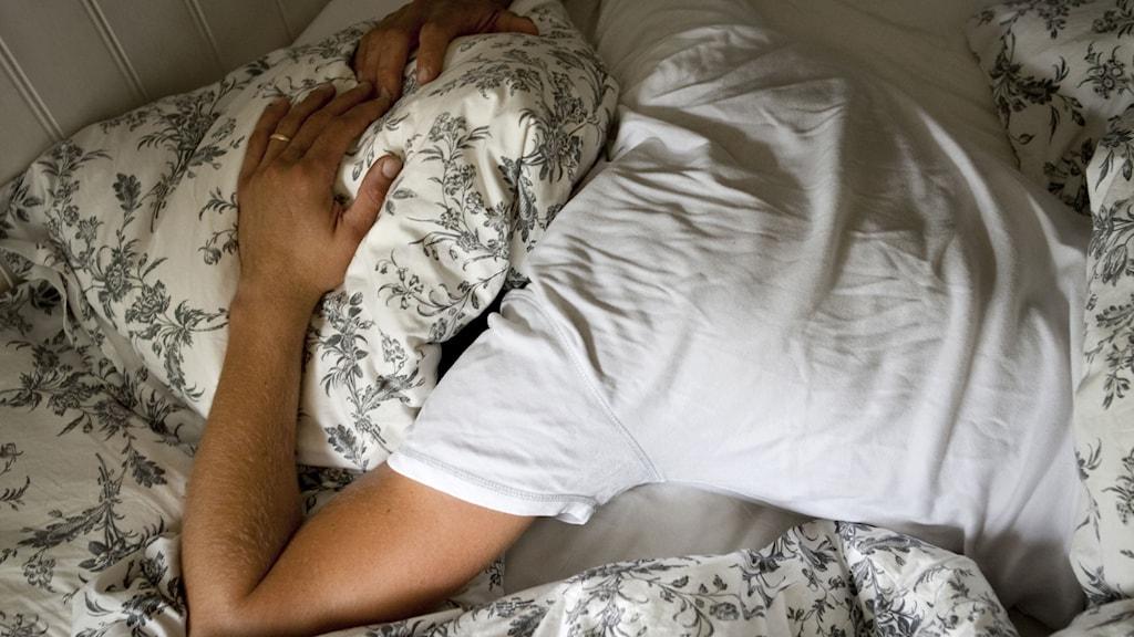 En man ligger utslagen i en säng med en kudde över huvudet. Foto: Christine Olsson/TT.
