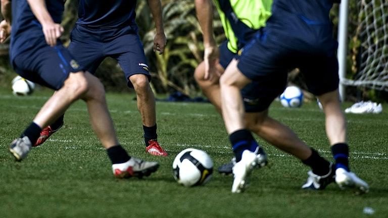 Fyra män som spelar fotboll.