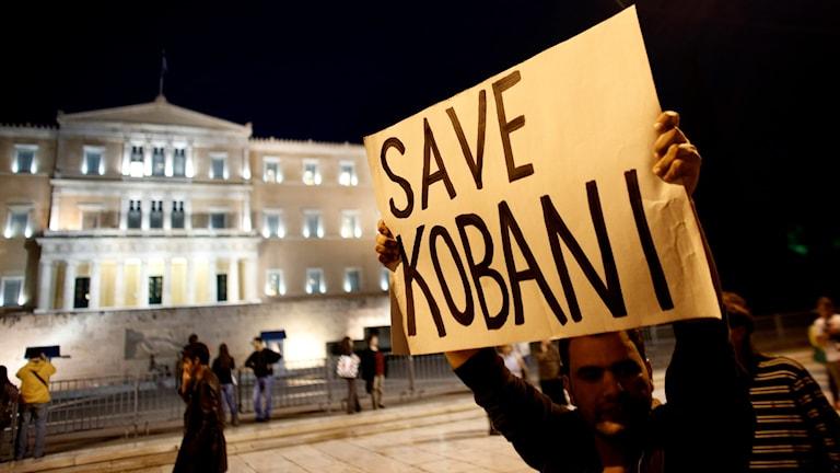 """Demonstrant håller upp ett plakat med """"Rädda Kobani""""."""