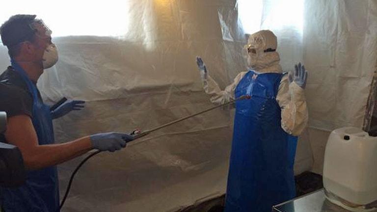 Det sprayas klor på en läkare i skyddsdräkt på ebolautbildning. Foto: Matilda Niang/Sveriges Radio.