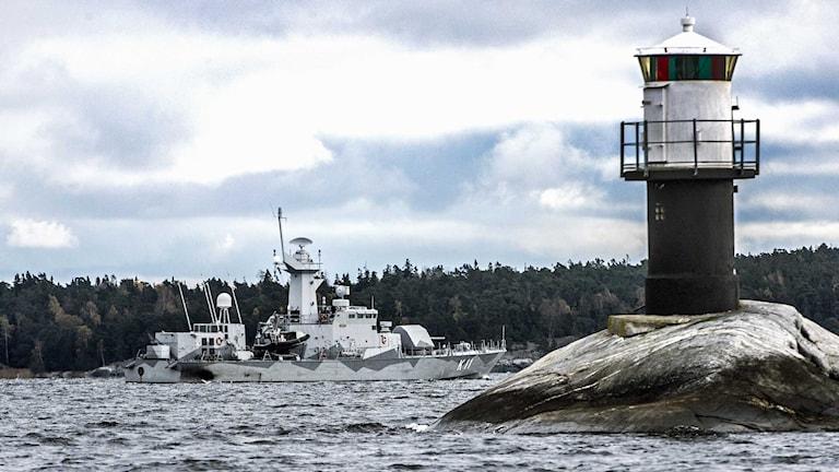 Ett militärt fartyg och en fyr i skärgården.
