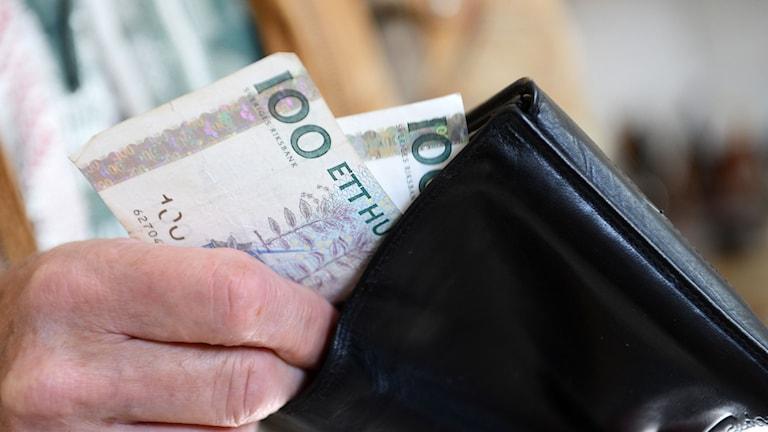 En man stoppar ner två hundralappar i sin plånbok Foto: Fredrik Sandberg/TT.