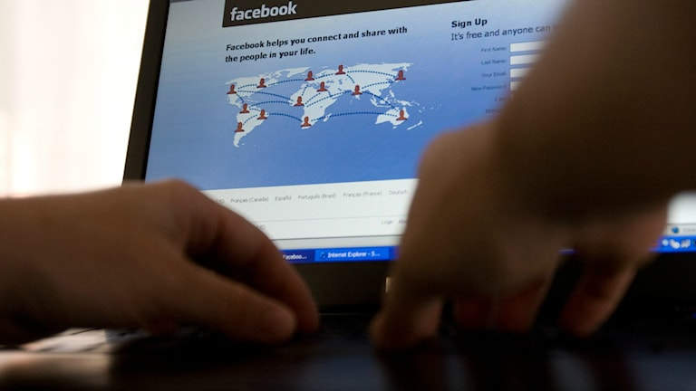 Händer på tangentbord framför skärm med Facebook på.