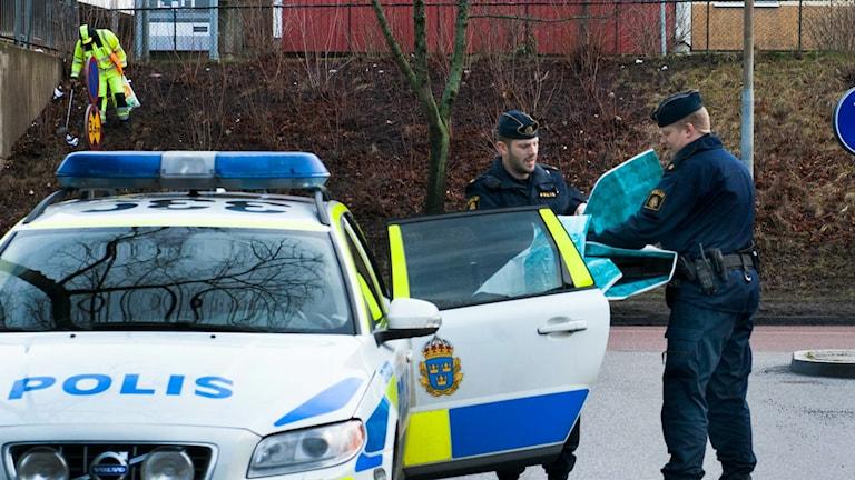 Två poliser utanför en polisbil
